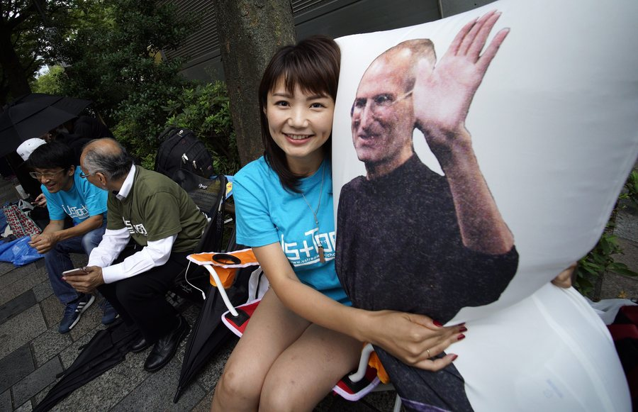 epa05541641 Apple enthusiast Ayano Tominaga poses with a pillow bearing an image of Apple co-founder Steve Jobs after she bought the new iPhone 7 at the Apple Store of Omotesando shopping district in Tokyo, Japan, 16 September 2016. Tominaga and other Apple fans were lined up for two days before the store to be the first to buy Apple's new smartphones.  EPA/FRANCK ROBICHON