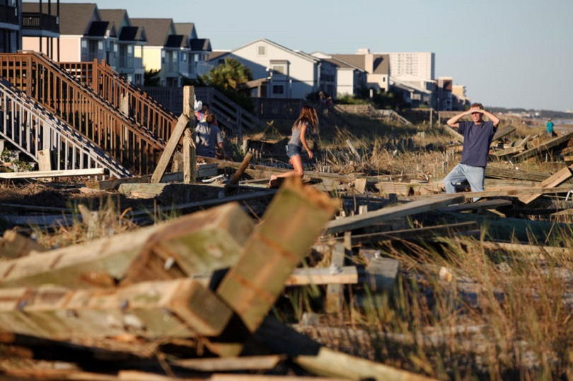 People look through the debris from the pier damaged by Hurricane Matthew in Surfside Beach